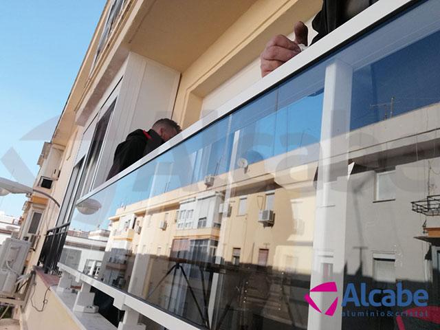 Colocación e instalación de Barandilla de Cristal para balcón o terraza, con pasamanos de aluminio lacado en blanco, en Los Remedios (Sevilla)