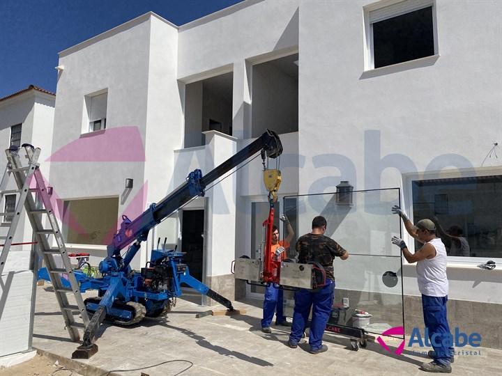 Elevación y colocación de cristales con minigrúa, en vivienda unifamiliar de Huelva