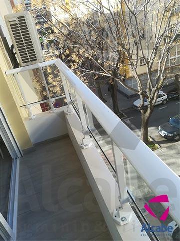 Barandilla de cristal en balcón, con pasamanos en aluminio (Los Remedios, Sevilla)