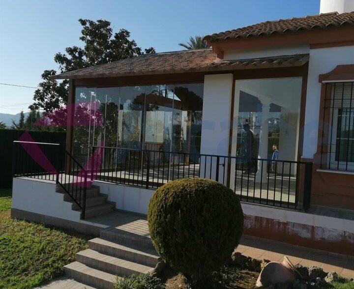 Instalación de estructura de aluminio con Techo de Panel de Teja a dos aguas y Cerramiento con Cortinas de Cristal en Córdoba